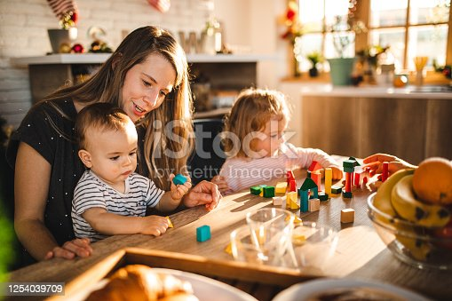 872316662 istock photo Baby boy and toddler girl spending creative morning with a mother during breakfast 1254039709
