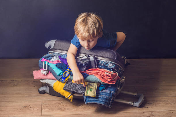 baby boy und reise-koffer. kind und gepäck verpackt für urlaub voller kleidung, kind und familie reise - kinderhandtaschen stock-fotos und bilder