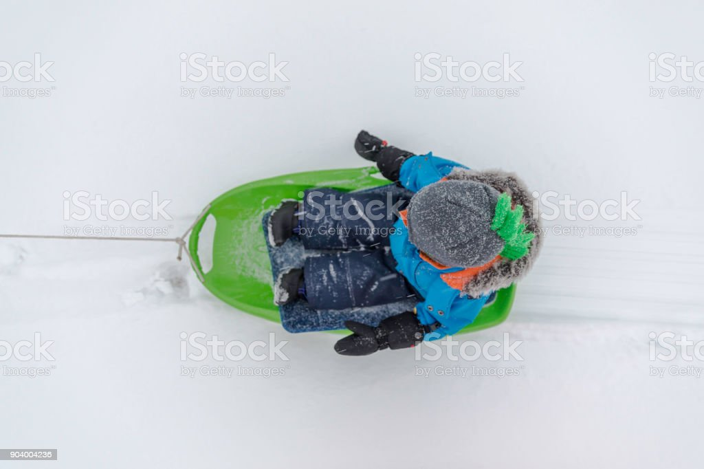 Baby Boy Being Pulled in Sleigh in Winter stock photo