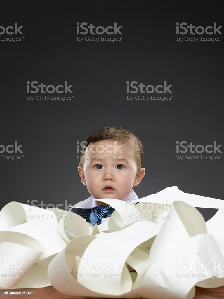 Baby boy (12-17 months) buried in paperwork, portrait royalty-free stock photo