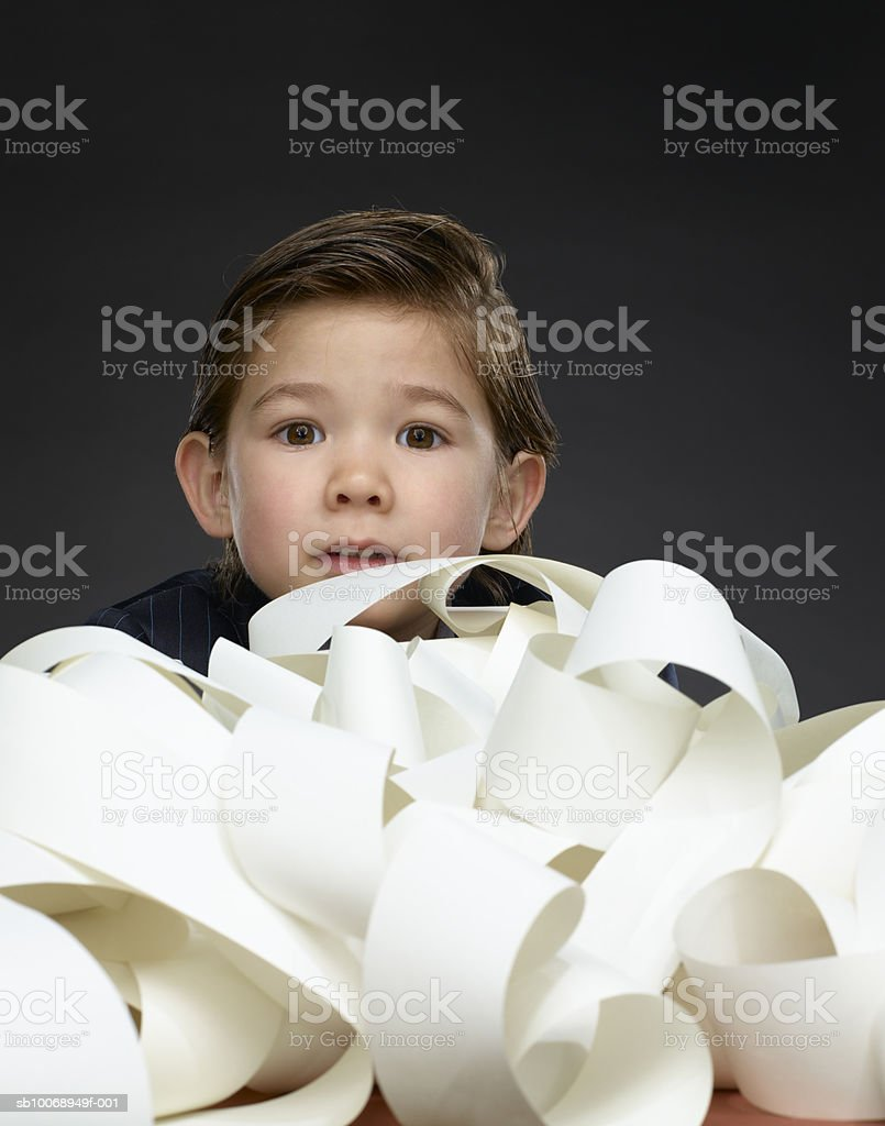 Baby boy (2-3) buried in paperwork, portrait Lizenzfreies stock-foto