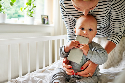 Baby Boy Chewing A Cellphone In Crib Stock Photo ...