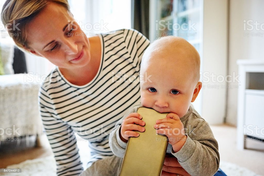 Baby boy chewing phone with his mother stock photo