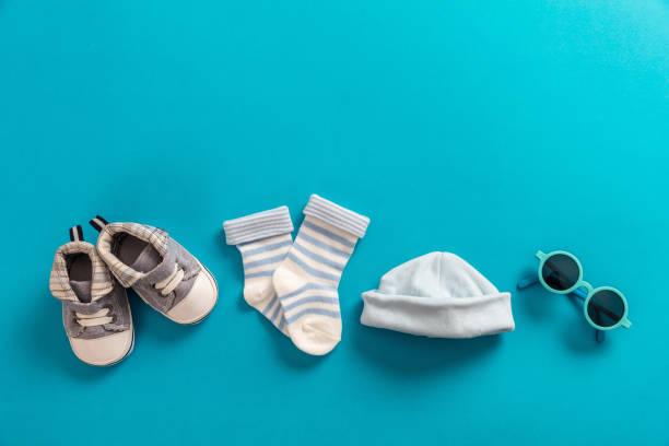 baby-kleidung und accessoires auf leuchtend blauem hintergrund - geschenk zur taufe stock-fotos und bilder