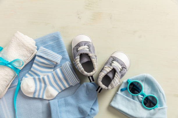 Baby boy clothes and accessories on wooden background Baby boy shower concept on wooden background, copy space, top view baby clothing stock pictures, royalty-free photos & images