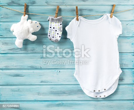 istock Baby boy clothes and white bear toy on a clothesline 527055994
