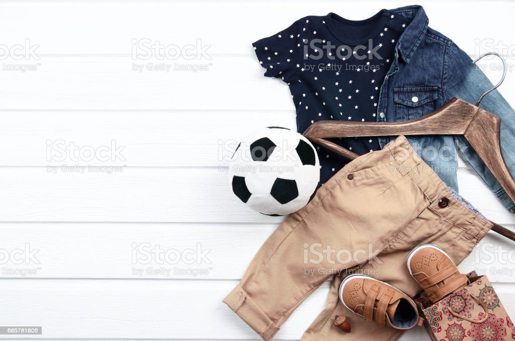 Baby boy clothing set (blue t-shirt with white stars, jeans shirt, brown shoes, pant). Wish list or shopping overview for pregnancy and baby shower. View from above. royalty-free stock photo