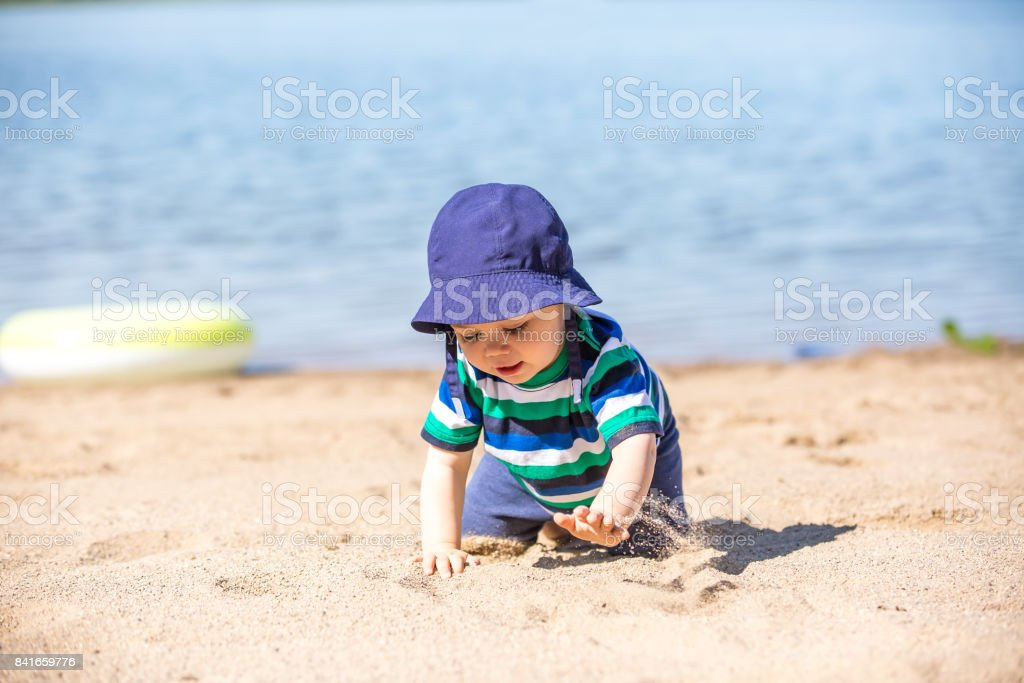 Baby Boy Crawling in Sand at Beach stock photo