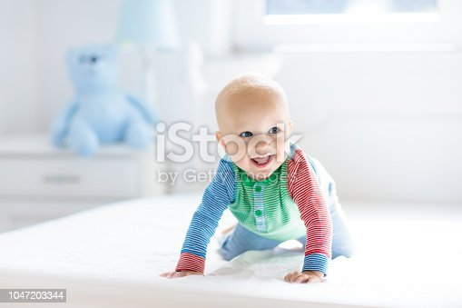 istock Baby boy crawling on bed 1047203344