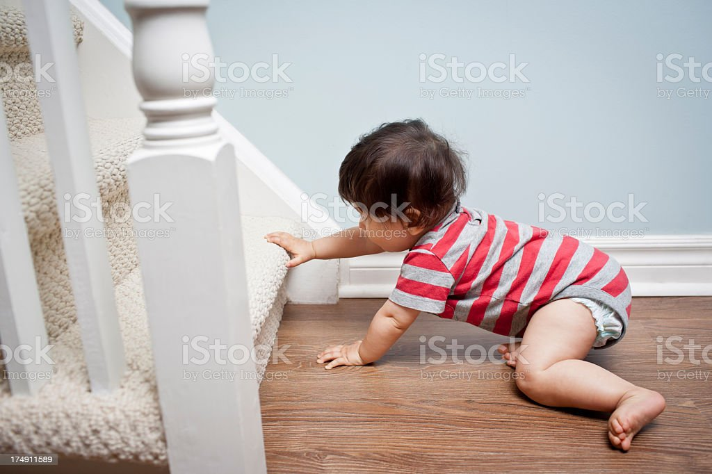 A baby boy crawling towards the stairs stock photo