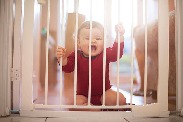 Baby boy crying at baby gate stock photo