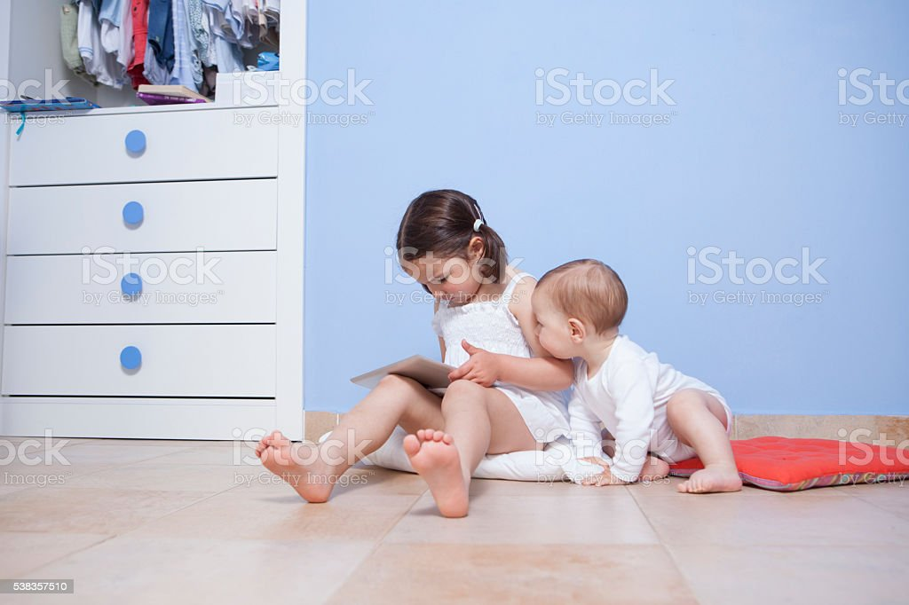 Baby boy discovering her sister tablet pc stock photo
