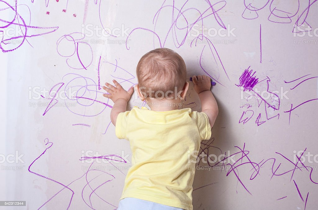 Baby boy drawing on plasterboard wall stock photo