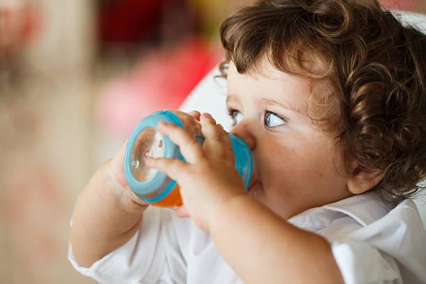baby boy (6-12 months) drinking from bottle - innocent saft stock-fotos und bilder
