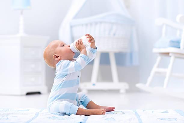 Baby boy drinking milk from a bottle in sunny nursery stock photo