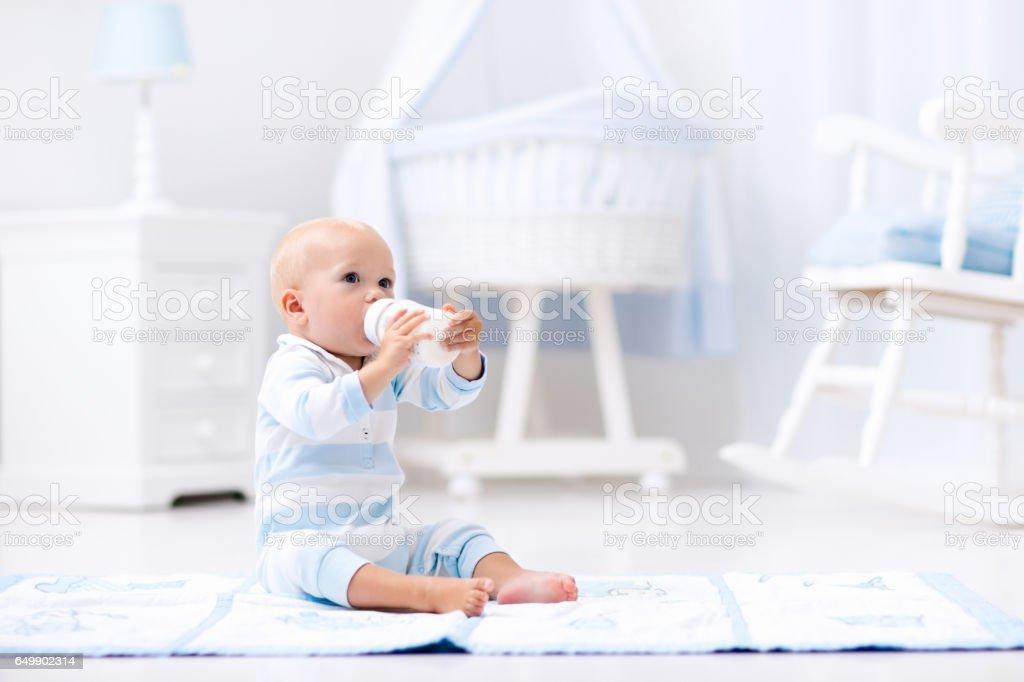 Baby boy drinking milk in sunny nursery圖像檔