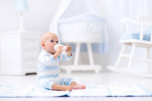 Babyjunge trinkt Milch in sonnigen nursery – Foto
