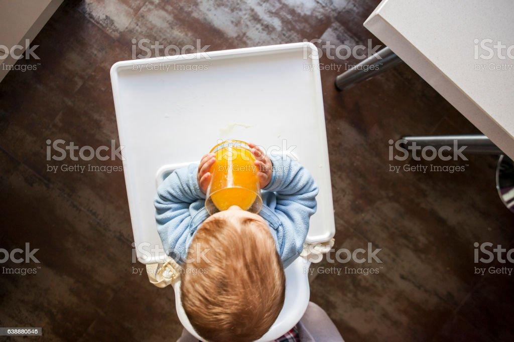 Baby boy drinking orange fresh juice stock photo