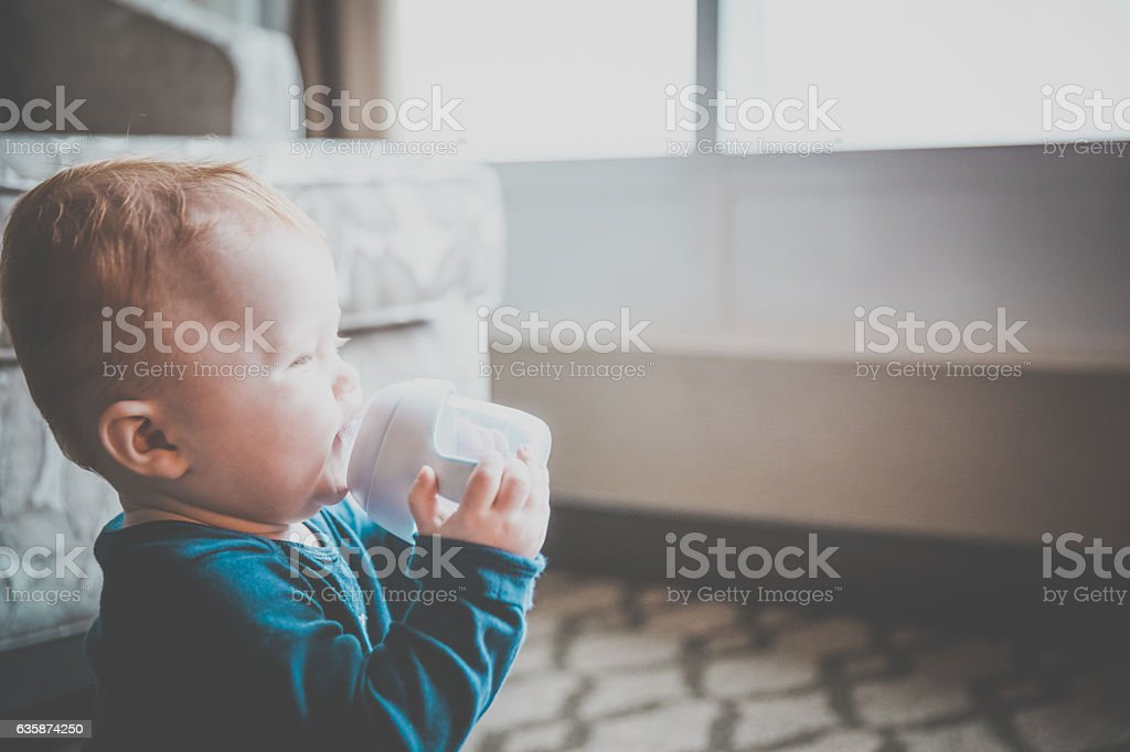 Baby Boy Drinking with Baby Bottle Alone stock photo