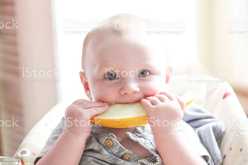 Baby Boy eating a Melon Slice stock photo