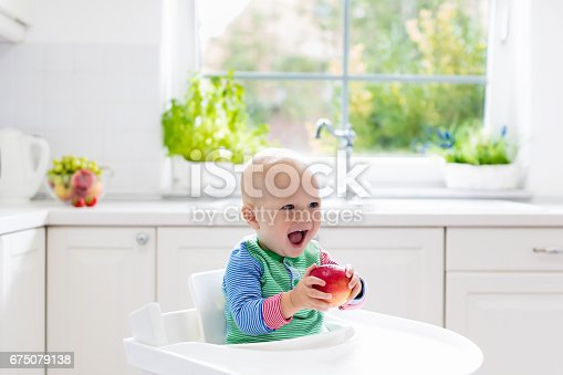istock Baby boy eating apple in white kitchen at home 675079138