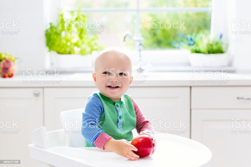 Baby boy eating apple in white kitchen at home foto de stock royalty-free