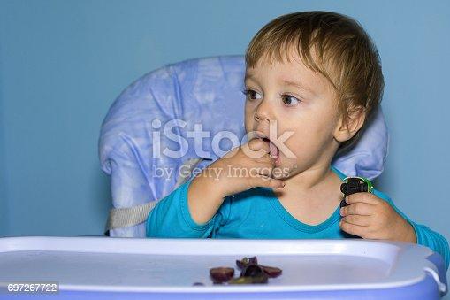 Baby boy eating black grapes.