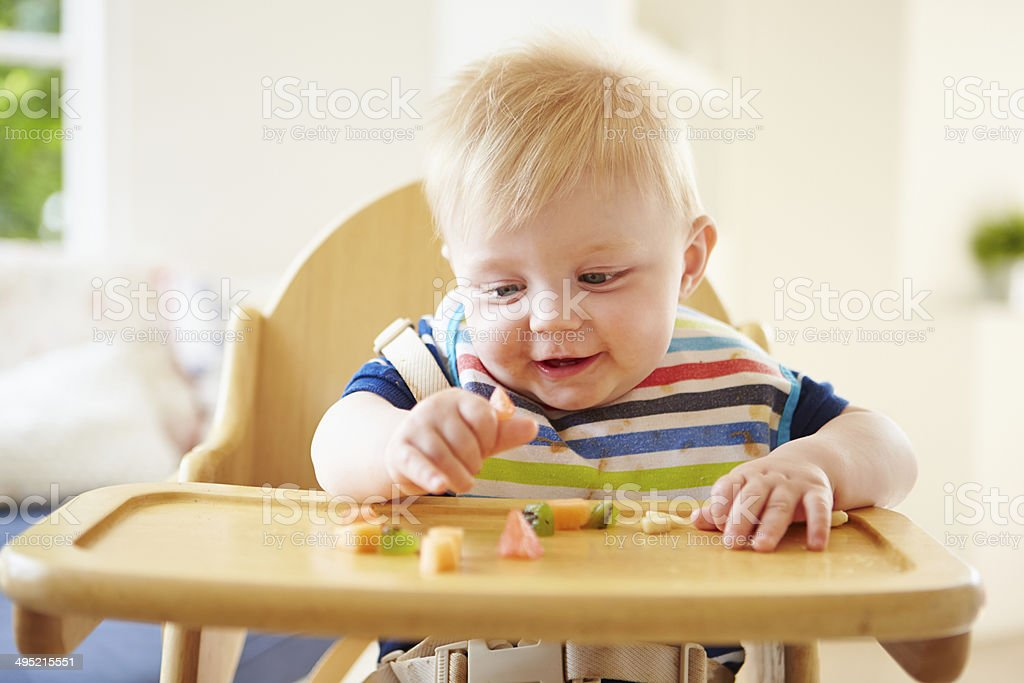 Baby Boy Eating Fruit In High Chair stock photo