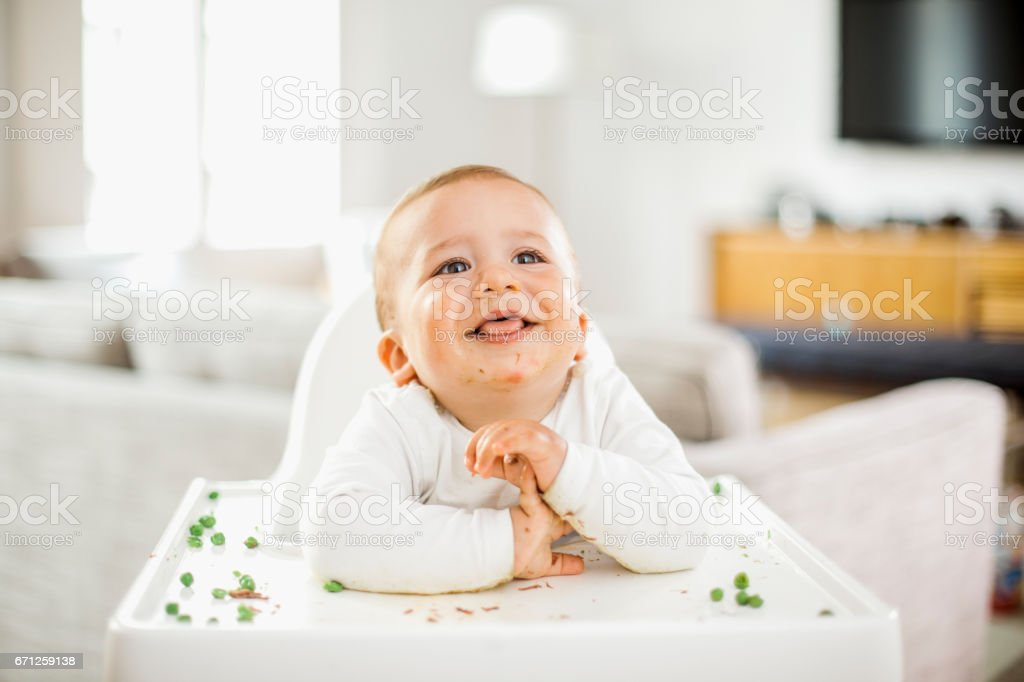 Baby boy eating green peas stock photo