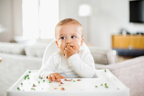 Baby junge grüne Erbsen essen – Foto