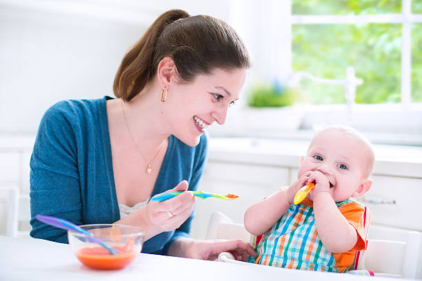 Baby boy eating his first solid food stock photo
