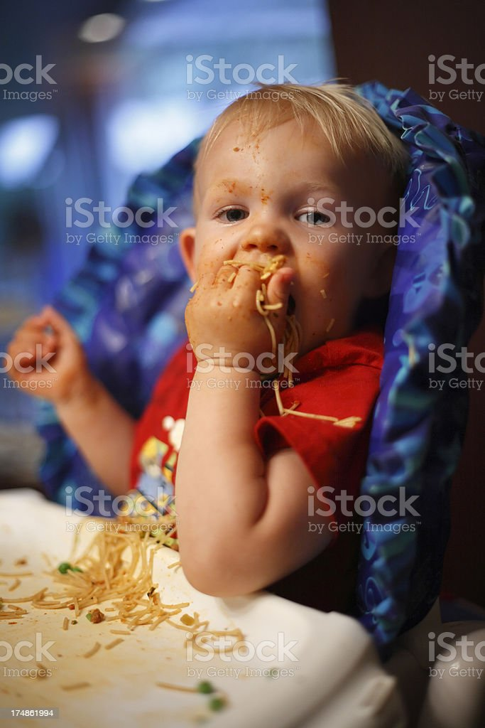 Baby boy eating pasta with his hand royalty-free stock photo
