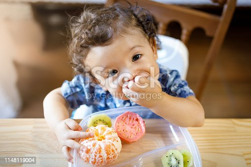 Baby eating fruits.