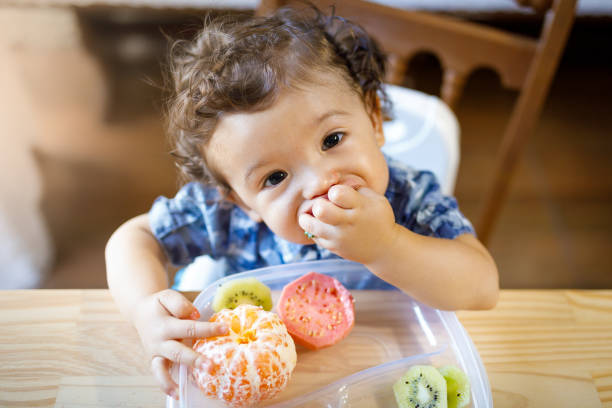 Baby boy eating tasty fruit stock photo