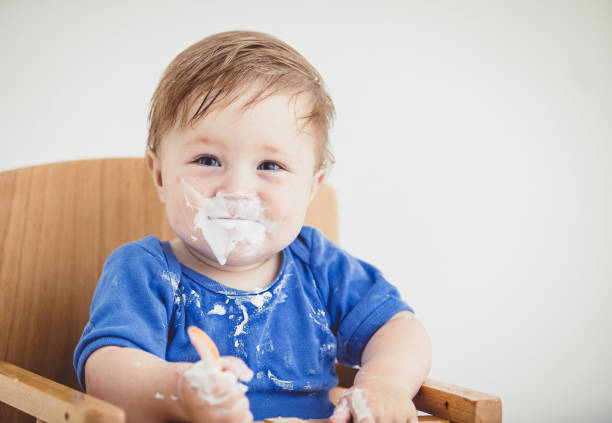 Baby Boy Eating Yoghurt With Spoon, Baby Led Weaning stock photo