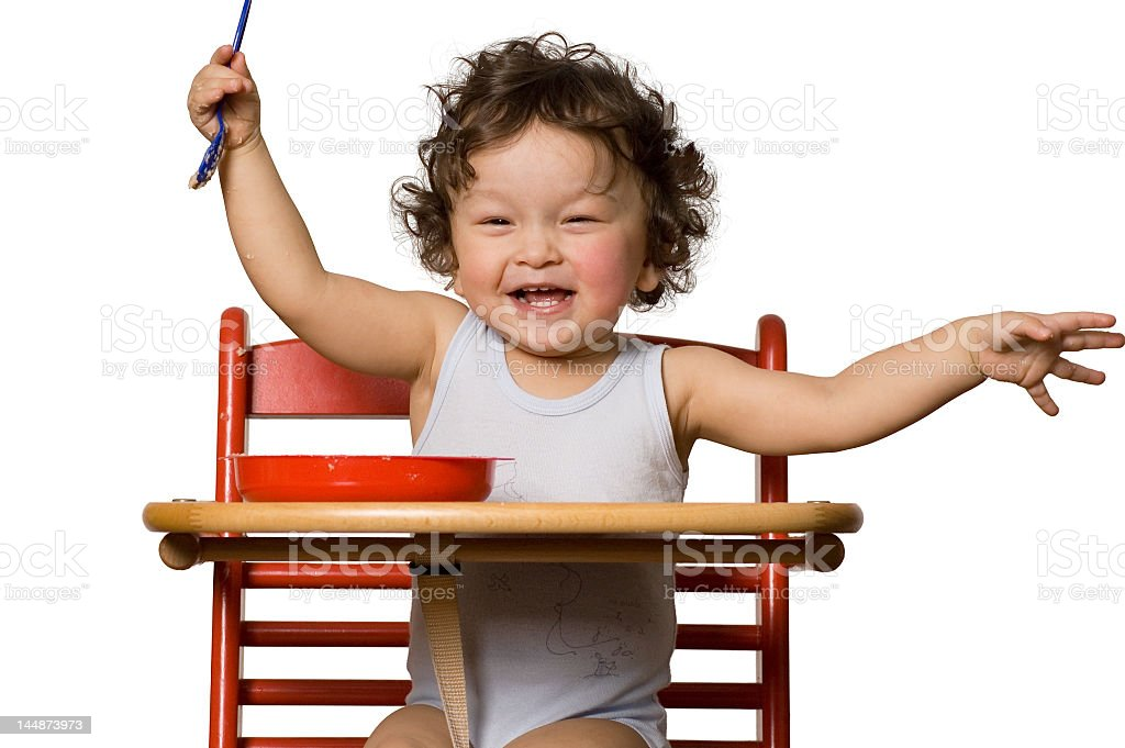 Baby boy enjoying his food in the highchair royalty-free stock photo