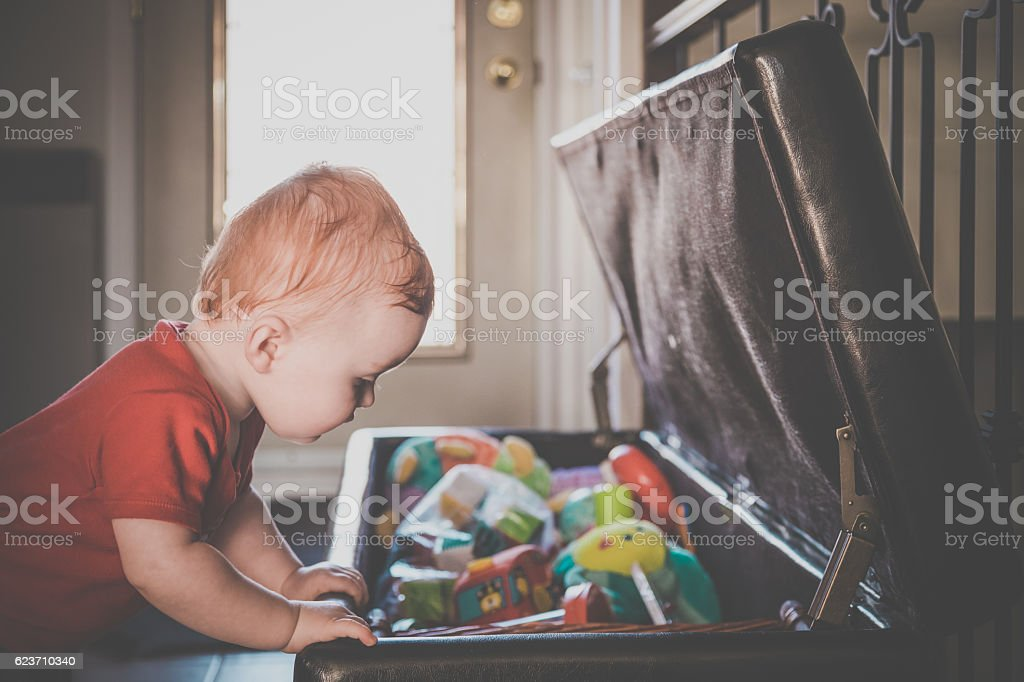 Baby Boy Exploring and Looking Inside Toy Box stock photo
