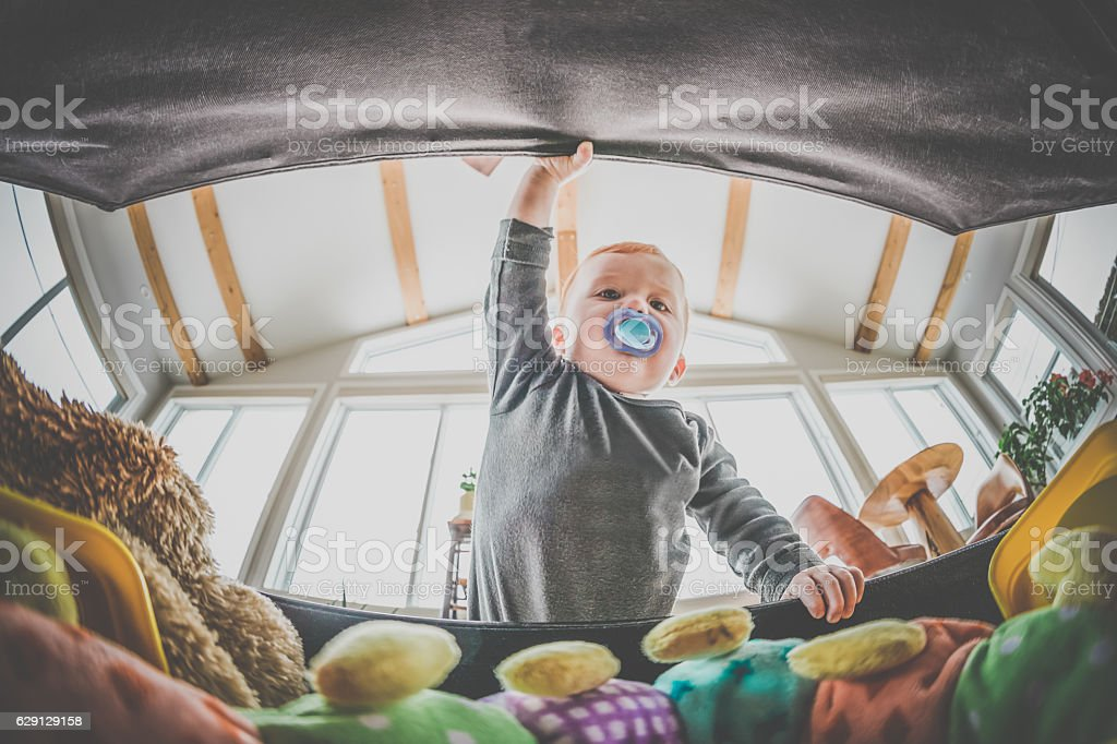 pov baby boy exploring and looking inside toy box stock