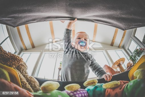 istock POV Baby Boy Exploring and Looking Inside Toy Box 629129158