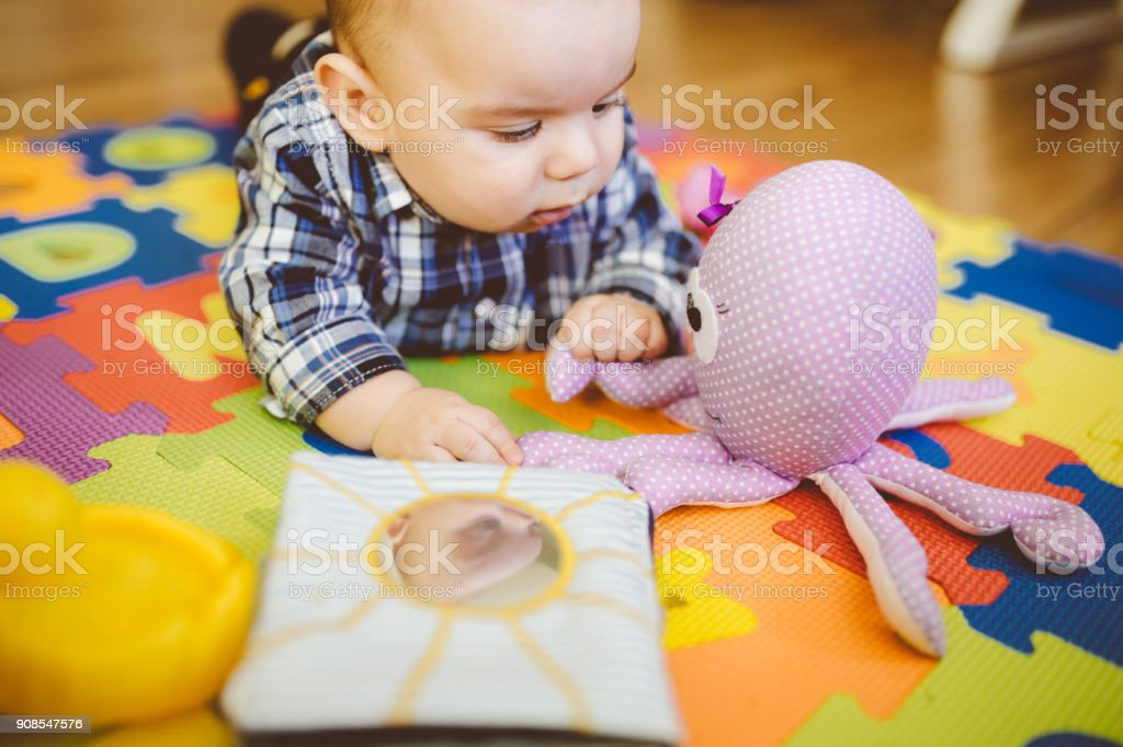 Baby Boy Flooring Surrounded By Lots Of Toys stock photo