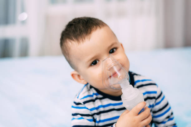 Baby boy holding a mask immobilizer sprayer while taking a breath Baby boy holding a mask immobilizer sprayer while taking a breath smoke inhalation stock pictures, royalty-free photos & images