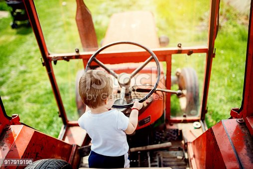 Baby boy holding a steering wheel of tractor. Growing up at a countryside.