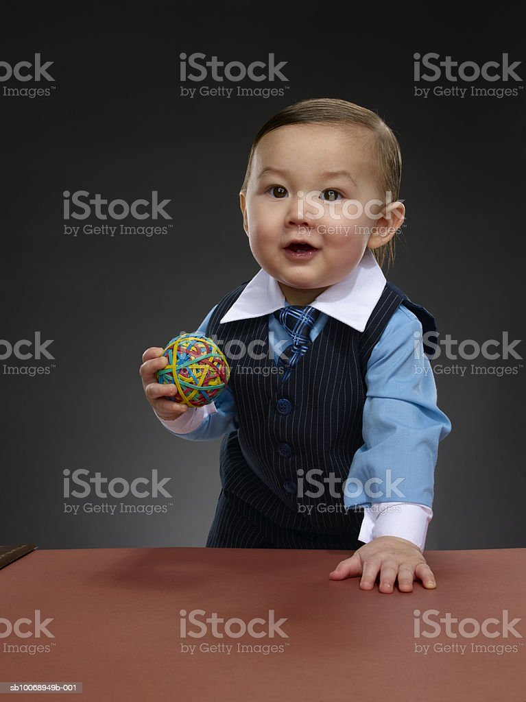 Baby boy (12-17 months) holding ball of colored rubber bands, portrait foto de stock libre de derechos