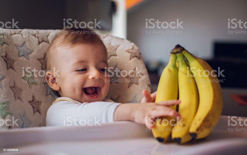 Baby boy holding bananas stock photo
