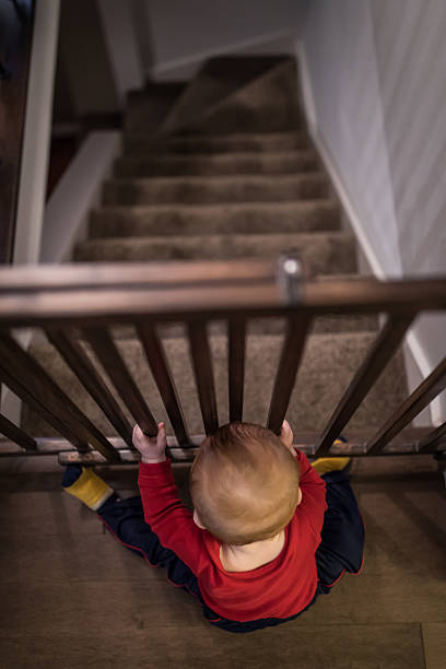 Baby Boy Holding Stair Gate stock photo