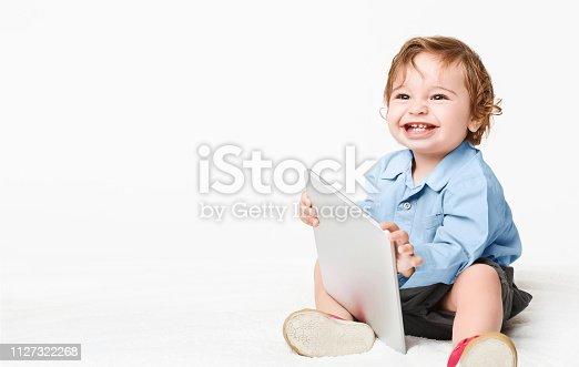 istock Baby boy holding tablet pc, studio background 1127322268
