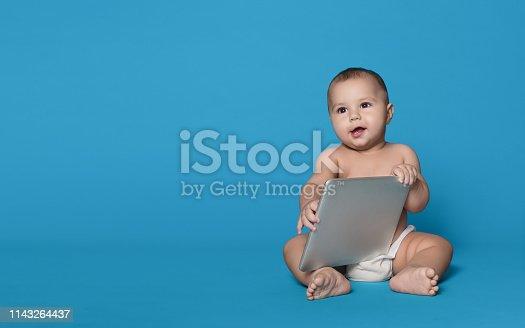istock Baby boy holding tablet pc, studio background 1143264437