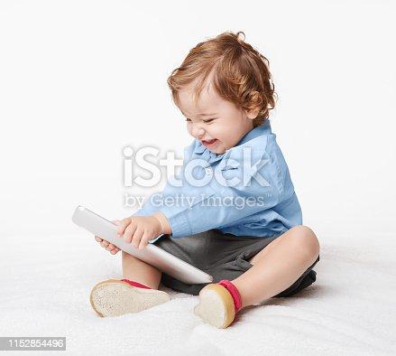 istock Baby boy holding tablet pc, studio background 1152854496