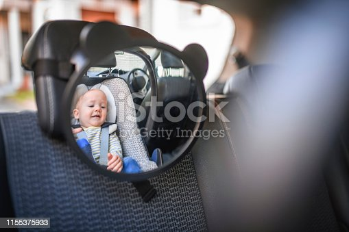 Shot of baby boy sitting in a car safety seat. He is happy and smiling.