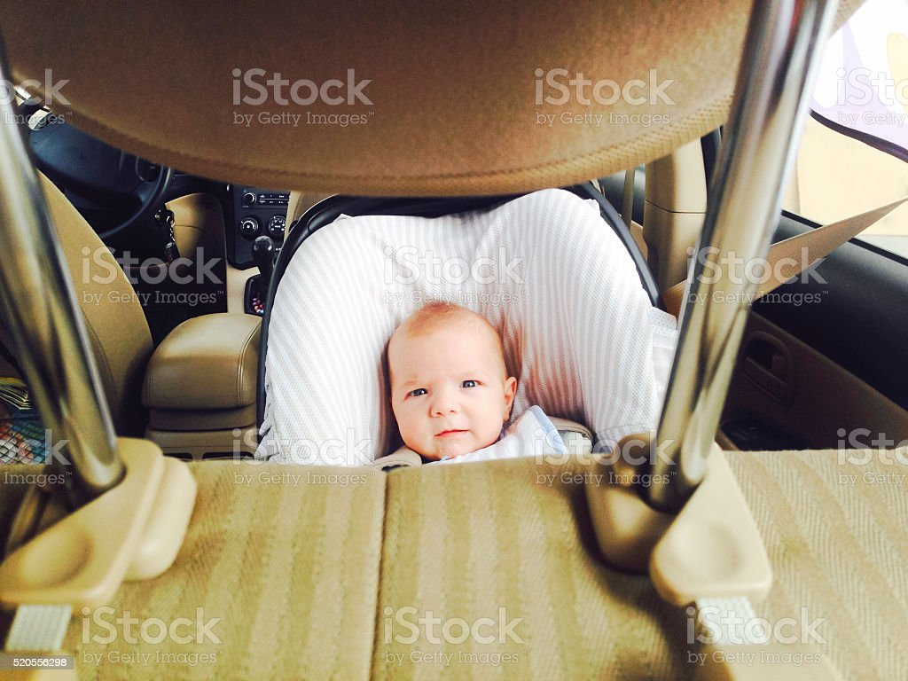 baby boy in a safety car seat stock photo